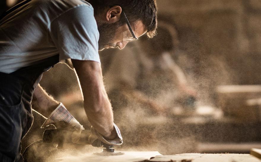 Mężczyzna szlifuje drewno